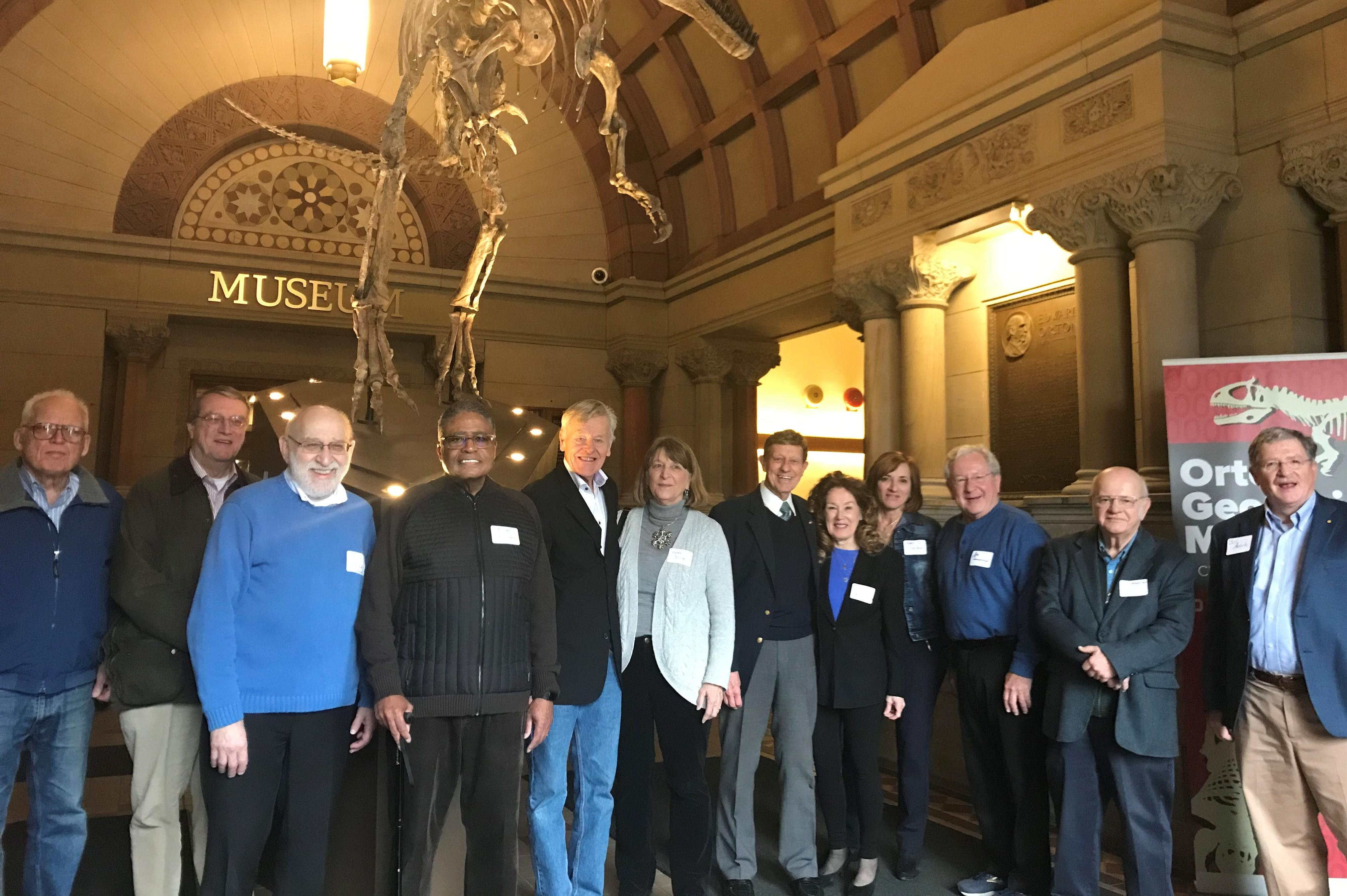 Emeritus Academy members gathered at a museum. Standing in front of a dinosaur skeleton.