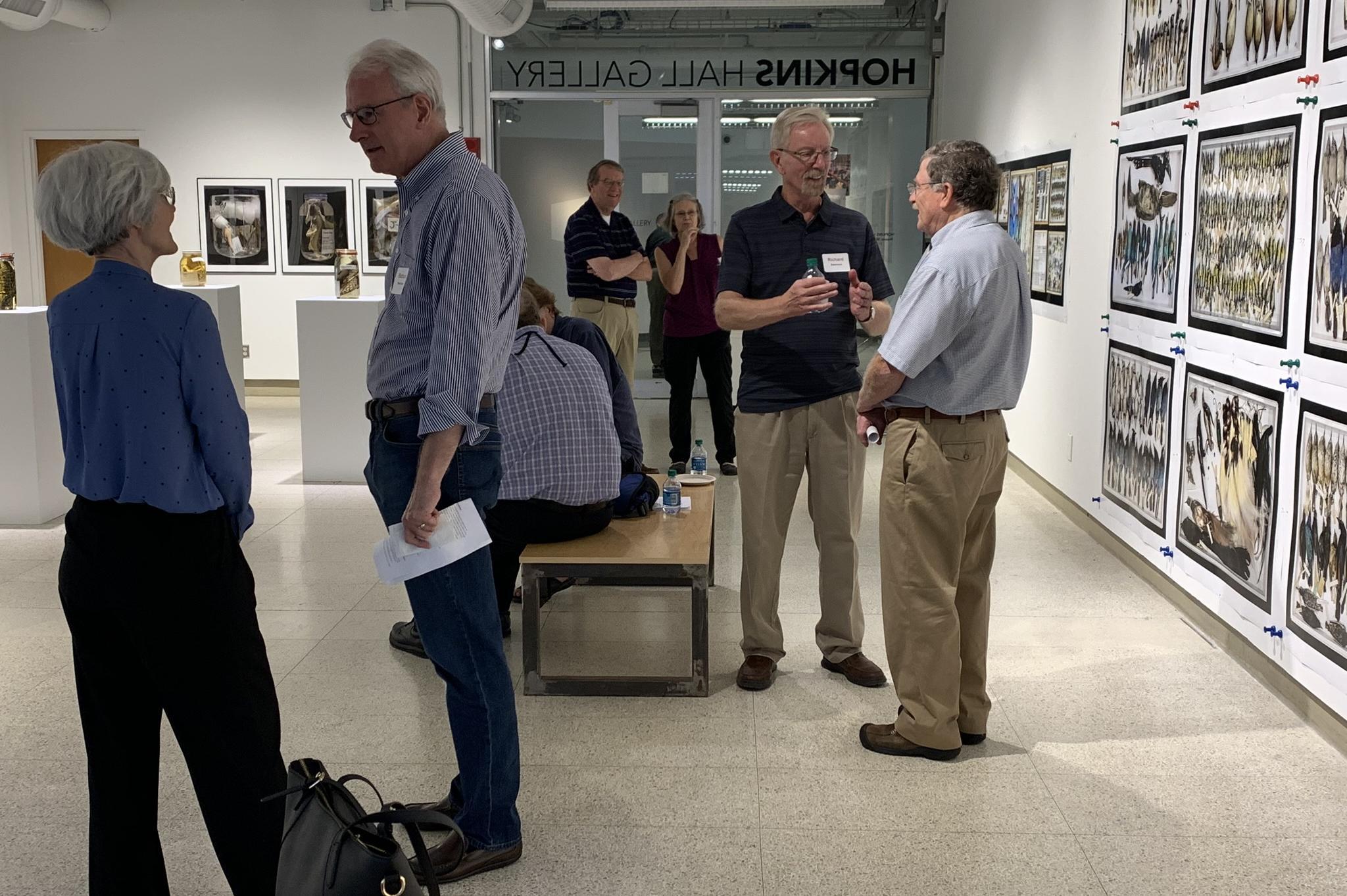 Emeritus Academy members and prospective members conversing in Hopkins Hall art gallery.